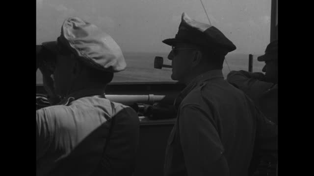 General Douglas MacArthur standing on deck of ship looking out General Richard Sutherland standing next to him looking through binoculars / different...