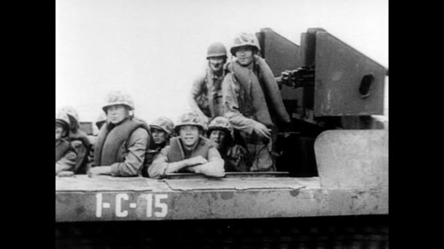 General Douglas MacArthur steps off plane and shakes hand with uniformed man / soldiers arriving by amphibious vehicle / aerial view of military...