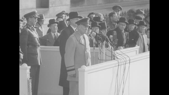 vídeos y material grabado en eventos de stock de general dwight d. eisenhower, wearing overcoat, stands at microphones in speaker's box built in front of city hall, addressing the algonquin regiment... - boina