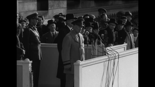 General Dwight D Eisenhower wearing overcoat stands at microphones in speaker's box built in front of City Hall addressing the Algonquin Regiment of...