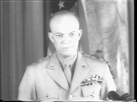 General Dwight Eisenhower applauding at New York Giants game at Polo Grounds / rain pouring down on grass / Eisenhower and group getting in out of...