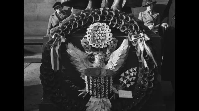 General Dwight Eisenhower lays a wreath and salutes Scottish National War Memorial at Edinburgh Castle / CU wreath of poppies with American eagle /...