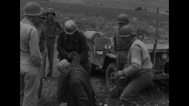 vídeos de stock, filmes e b-roll de us general dwight eisenhower looking at german booby trap held by officer / jeep driving down hill carrying german soldier and wounded german officer... - dwight eisenhower