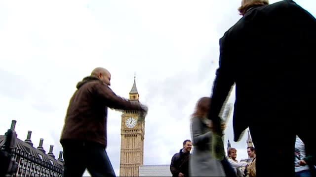 flashmob in parliament square supports hung parliament england london parliament square ext young women rolling up newspapers / members of flashmob... - flash mob stock videos and b-roll footage