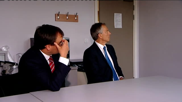 tony blair visits harrow clinic tony blair takes seat at meeting table and health centre manager shows him slide projection with statistics about... - harrow stock videos & royalty-free footage