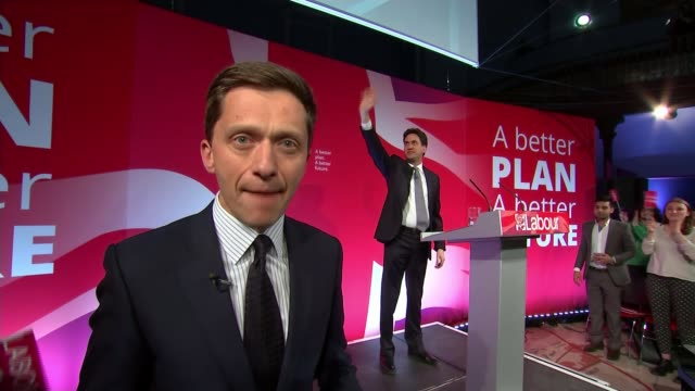 labour ed miliband campaigning in leeds reporter to camera with miliband in background - ウェストヨークシャー点の映像素材/bロール