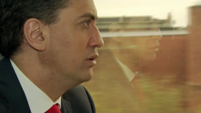 stockvideo's en b-roll-footage met possible postelection deals / child benefit row wales cardiff int ed miliband seated on train chatting with unidentified man as pulling into cardiff... - mogelijk