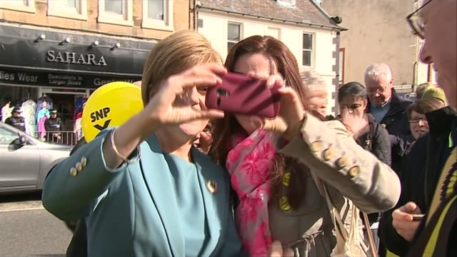 stockvideo's en b-roll-footage met possible postelection deals / child benefit row scotland musselburgh ext nicola sturgeon posing for selfie photographs with supporters during... - mogelijk