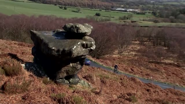 report from the yorkshire dales reporter cycling along country road reporter on millstone grit formation of brimham rocks bv couple sitting on rock - millstone stock videos & royalty-free footage