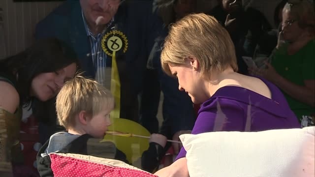 general election 2015: snp campaign: sturgeon campaigns in edinburgh; sturgeon seen through window sat with young child eating lollipop - lollipop stock videos & royalty-free footage