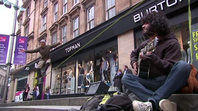 general election 2015: snp wins 56 of 59 seats in scotland; street entertainer walking tightrope as busker heard singing busker singing people along... - tightrope walking stock videos & royalty-free footage