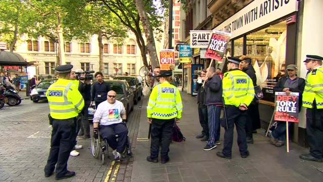 theresa may arriving at lbc england london leicester square ext group of antitory protesters one using loudspeaker sot / protesters with placards... - motorcade stock videos & royalty-free footage