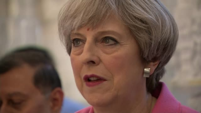 tory confusion over income tax policy england london int theresa may and her husband philip pouring liquid from small golden vessels over statue of... - itv weekend late news点の映像素材/bロール