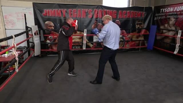 vidéos et rushes de boris johnson visits boxing gymnasium england manchester wythenshawe int boris johnson along into boxing ring / johnson having boxing gloves put on /... - élection