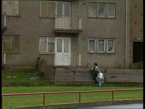 vídeos de stock e filmes b-roll de alienation of the poor itn scotland glasgow blairtummock housing estate large hole in roof of boarded up building on poor housing estate ls child... - glasgow escócia