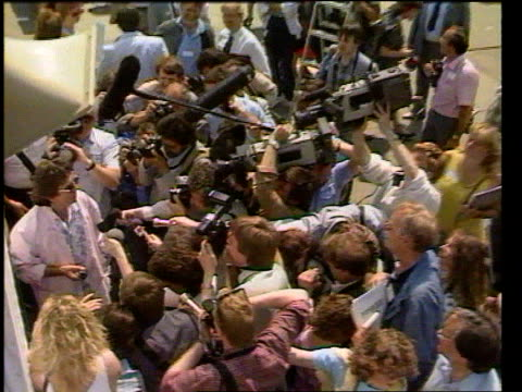 celebrities tx lts george harrison surrounded by people and press zoom in tcms harrison about to write with market pen - george harrison video stock e b–roll
