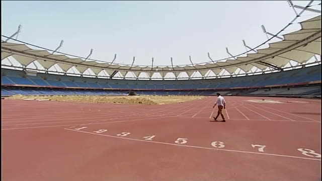 vidéos et rushes de expected defeat for ruling 'congress' party day reporter along inside abandoned stadium bird landing on pile of sand and reporter along empty seats... - a l'abandon