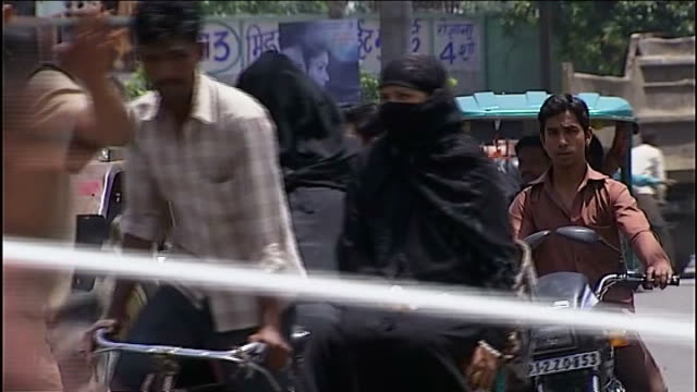 expected defeat for ruling 'congress' party; delhi: bicyles and vehicles along on road muslim women along on vehicle in burkas children along at... - 僧衣点の映像素材/bロール