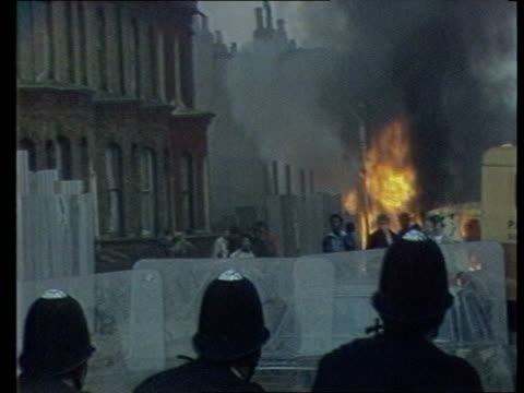 Law and order issues General election Law and order issues TX 2891985 London Brixton EXT Police with riot shield b/g fires youths in streets...
