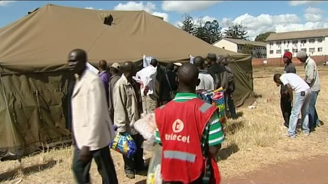 morgan tsvangirai declares vote a 'huge farce'; zimbabwe: harare: ext crowd of people stand looking at leaflet pinned to polling statino tent showing... - see other clips from this shoot 412 stock videos & royalty-free footage