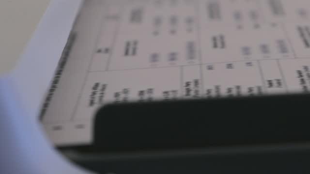 vídeos de stock e filmes b-roll de us general election processing voter ballots through a digital vote tabulator counting machine 4k video series - escrutínio