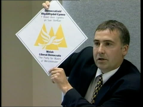 wales plaid cymru manifesto welsh liberal democrats press conference man holding up poster supporting welsh liberal democrats member of the welsh... - plaid stock videos & royalty-free footage