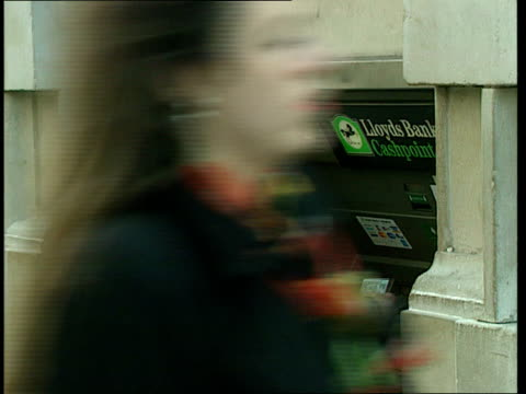 Economic policies ITN ENGLAND London People along street Woman at Lloyds Bank cash dispenser People along street People drinking in cafe People along...