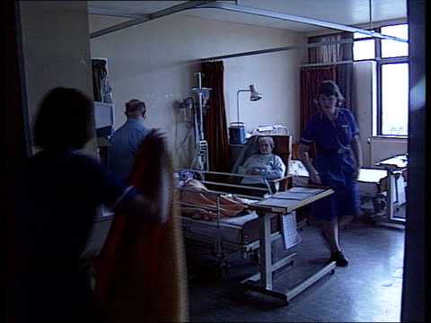 health bv porter wheeling patient in trolley along corridor ms ward as nurse in with blanket ms corridor cms nurse puts bed jacket on woman patient - porter stock videos & royalty-free footage