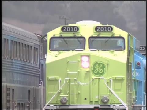 general electric's hybrid train moves along a track. - ジェネラルエレクトリック点の映像素材/bロール