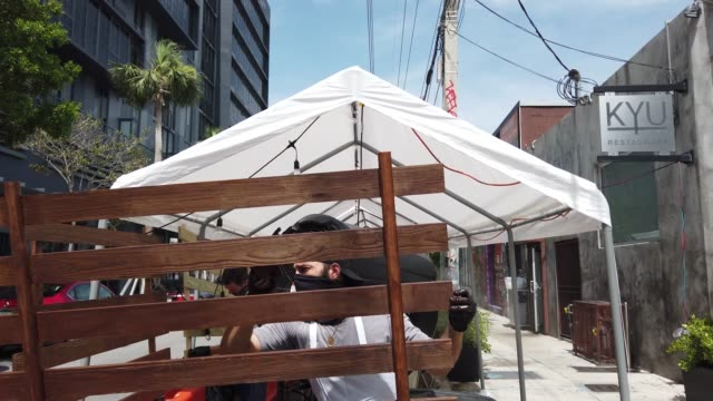 general footage as restaurant staff prepares a newly constructed outdoor seating area for guests at the kyu restaurant in wynwood on july 09 2020 in... - miami dade county stock videos & royalty-free footage
