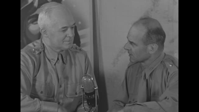 General Henry Hap Arnold Commanding General of US Army Air Forces on left sitting at desk with Gen Jimmy Doolittle / closer view of Doolittle talking...