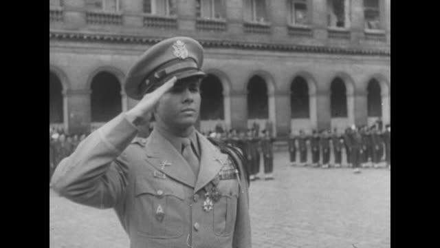 General Jean de Lattre de Tassigny awards medal to US officer Audie Murphy in ceremony in courtyard in Paris / De Lattre kisses Murphy on cheek /...