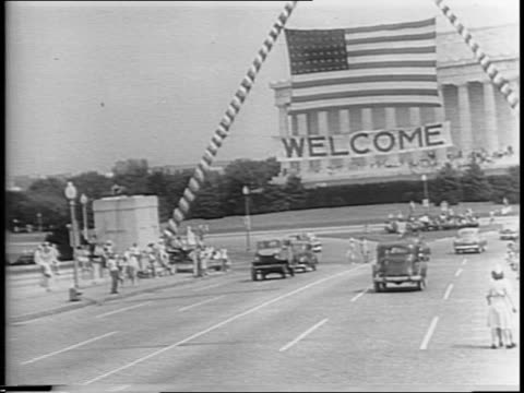 vídeos de stock e filmes b-roll de general jonathan wainwright waves from a car rides across the potomac under a welcome home banner and flag / montage at the washington monument a... - regresso ao lar