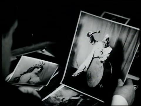 vídeos y material grabado en eventos de stock de general manager giulio gatti-casazza looking through photographs of operatic greats holding photograph of enrico caruso as the clown pagliacci new... - 1935