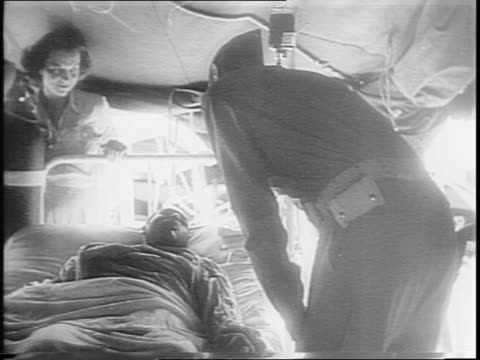 General Mark Clark Commander of US Fifth Army walks towards tents enters / visits wounded members of 92nd Infantry Division in a field hospital /...