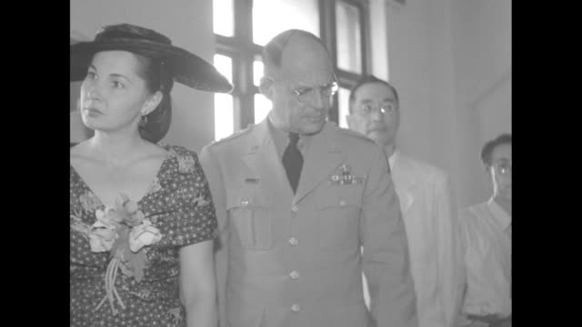 US General Matt Ridgway and wife Penny enter room of Tokyo National Museum along with officials and other officers / CU Ridgway looking at painting...