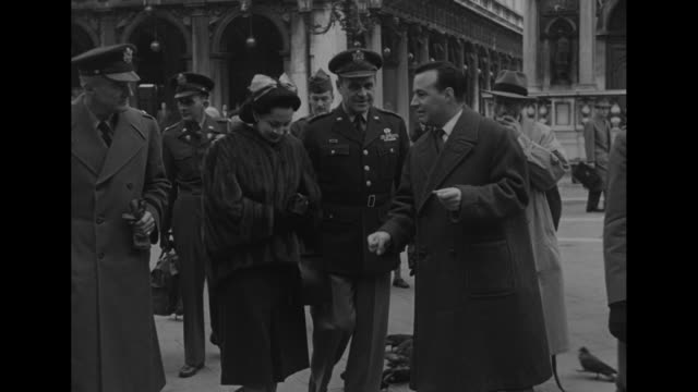 General Matthew Ridgway and his wife Penny in mink jacket another woman and military entourage walk up Venice street with Cathedral of San Giorgio...
