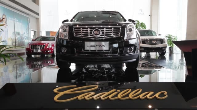 General Motors Co Cadillac SRX left and Escalade Hybrid sports utility vehicle are displayed at a dealership in Shanghai General Motors Co Cadillac...