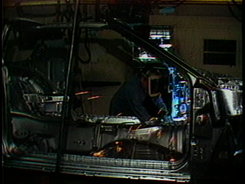 stockvideo's en b-roll-footage met general motors employees work on a car chassis in an assembly line. - chassis