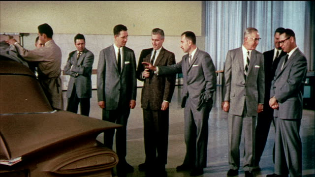 1958 montage ms zi ha zo general motors executives reviewing new model of car, senior executives shake hands / usa / audio - 1958年点の映像素材/bロール