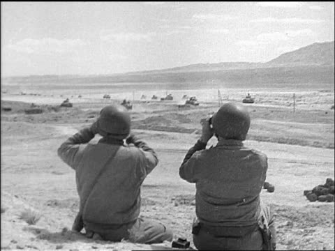 general patton + other man looking at tanks with binoculars / tunisia / documentary - 1943 stock-videos und b-roll-filmmaterial
