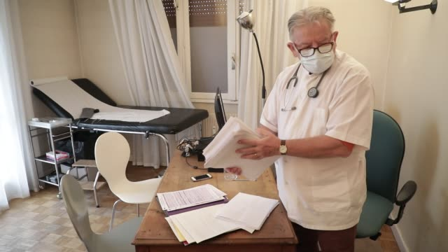 general practitioner working while wearing a health mask at his medical office in the middle of the covid19 pandemic crisis on march 22, 2020 in... - stetoskop bildbanksvideor och videomaterial från bakom kulisserna