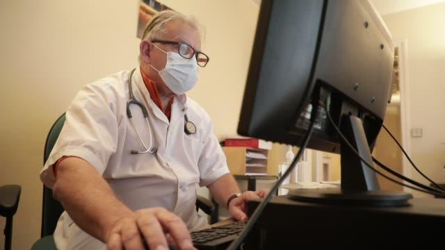general practitioner working while wearing a health mask at his medical office in the middle of the covid19 pandemic crisis on march 22, 2020 in... - 社会保障点の映像素材/bロール