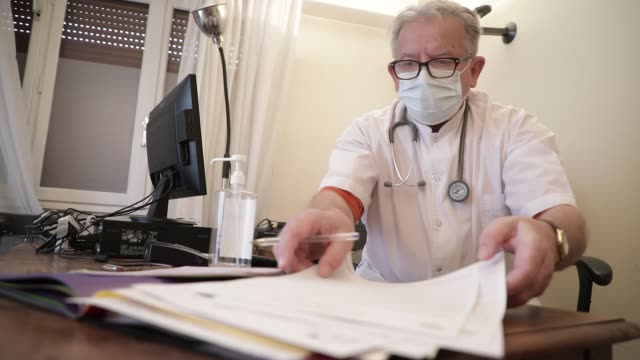 general practitioner working while wearing a health mask at his medical office in the middle of the covid19 pandemic crisis on march 22, 2020 in... - privacy video stock e b–roll