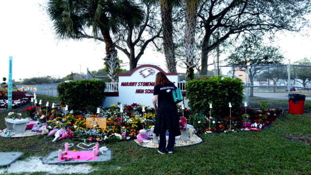 general shots of a memorial setup outside marjory stoneman douglas high school as people remember those lost during a mass shooting at the school on... - gedenkveranstaltung stock-videos und b-roll-filmmaterial