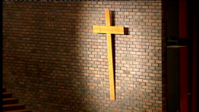 general synod meeting underway wooden cross on wall vicar holding small child - synod stock videos & royalty-free footage