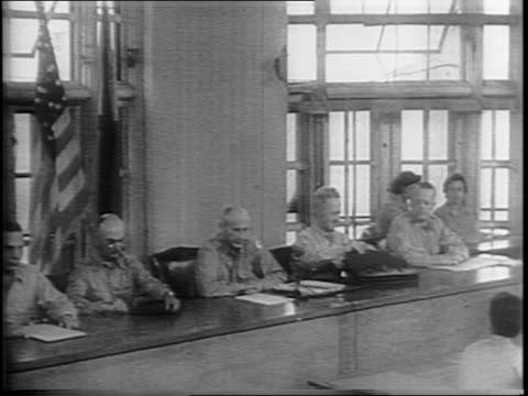 General Tomoyuki Yamashita takes his seat in the courtroom / General Russell Burton Reynolds speaks from table next to other US military commission...