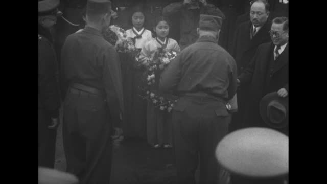 General Van Fleet receiving flowers from young girls South Korean dignitaries bowing /shaking hands with officers