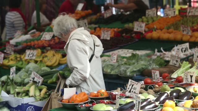vídeos de stock, filmes e b-roll de general view a fruit and vegetable market stall in lewisham south london uk on wednesday june 25 an elderly woman looks at cucumbers displayed for... - produto interno bruto