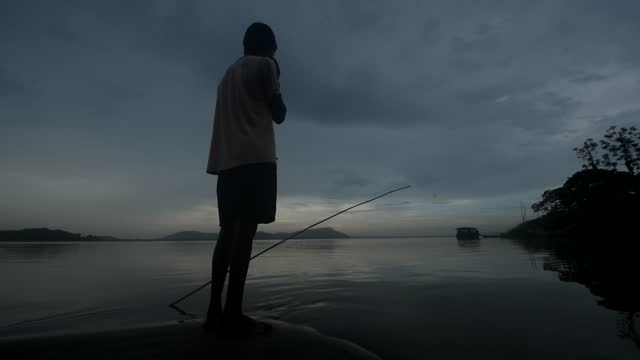 general view as a boy fishes in the brahmaputra river during a cloudy day on may 26, 2021 in guwahati, india. assam and other parts of northeast... - teenage boys stock videos & royalty-free footage